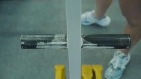 Chica joven, estructura atl?tica, entrenando en el gimnasio Ella va al estante de la barra y toma uno de ellos metrajes