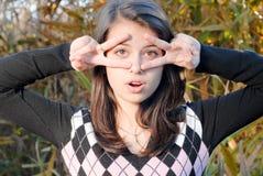 Chica joven feliz al aire libre que muestra la muestra de los vidrios Foto de archivo libre de regalías