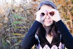 Chica joven feliz al aire libre que muestra un binocular Imagenes de archivo