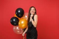 Chica joven feliz alegre bonita en poco vestido negro que celebra sosteniendo los balones de aire aislados en fondo rojo brillant fotografía de archivo libre de regalías