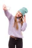 Chica joven feliz con el casquillo en el selfie que toma principal del teléfono (foto de sí misma) en el fondo blanco Fotos de archivo libres de regalías