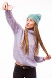 Chica joven feliz con el casquillo en el selfie que toma principal del teléfono (foto de sí misma) en el fondo blanco Imagen de archivo