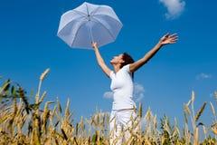 Chica joven feliz con el paraguas en el campo Imagenes de archivo