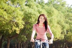 Chica joven feliz con el retrato al aire libre de la bicicleta. Fotografía de archivo