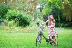 Chica joven feliz con la bicicleta y las flores Imagen de archivo libre de regalías