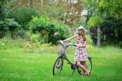 Chica joven feliz con la bicicleta y las flores Fotografía de archivo libre de regalías