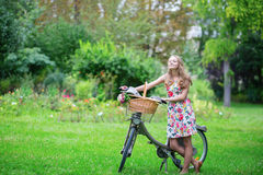Chica joven feliz con la bicicleta y las flores Imagen de archivo