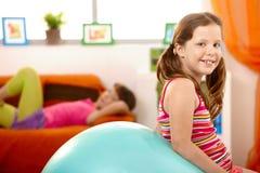 Chica joven feliz con la bola de la gimnasia Foto de archivo