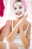 Chica joven feliz con la máscara facial cosmética Foto de archivo