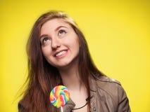 Chica joven feliz con la piruleta en un amarillo Imagen de archivo