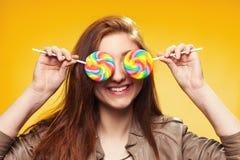 Chica joven feliz con la piruleta en un amarillo Fotografía de archivo libre de regalías