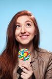 Chica joven feliz con la piruleta en un azul Fotos de archivo libres de regalías