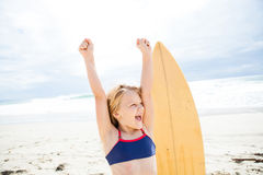 Chica joven feliz con la tabla hawaiana en la playa Fotografía de archivo