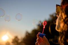 Chica joven feliz con las burbujas de jab?n en oto?o en la puesta del sol fotografía de archivo