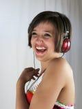 Chica joven feliz con los auriculares Fotos de archivo