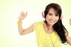 Chica joven feliz con los auriculares Imagen de archivo