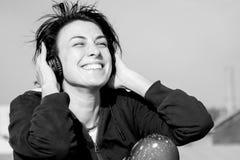 Chica joven feliz con los auriculares que escucha la música en el tejado y la sonrisa Foto de archivo libre de regalías