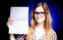 Chica joven feliz con los vidrios del empollón que sostienen el libro de ejercicio Imagen de archivo
