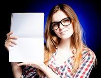 Chica joven feliz con los vidrios del empollón que sostienen el libro de ejercicio Foto de archivo libre de regalías