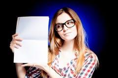 Chica joven feliz con los vidrios del empollón que sostienen el libro de ejercicio Imágenes de archivo libres de regalías