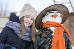Chica joven feliz con un muñeco de nieve, cierre para arriba Imagen de archivo libre de regalías