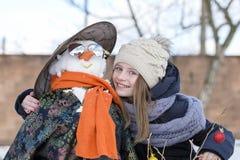 Chica joven feliz con un muñeco de nieve, cierre para arriba Imagen de archivo