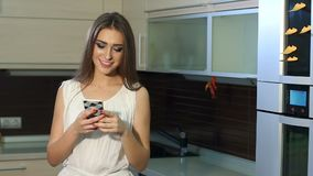 Chica joven feliz con un teléfono en sus manos que bailan en la cocina en casa almacen de metraje de vídeo