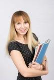 Chica joven feliz con una carpeta en sus manos que sonríe feliz en la imagen Imágenes de archivo libres de regalías
