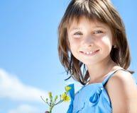 Chica joven feliz con una flor en su mano Imagen de archivo libre de regalías