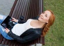 Chica joven feliz con una tableta y una taza de café Imagen de archivo