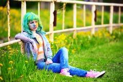 Chica joven feliz del retrato en festival del color del holi sobre una cerca vieja Fotografía de archivo