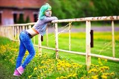 Chica joven feliz del retrato en festival del color del holi sobre una cerca vieja Fotos de archivo libres de regalías
