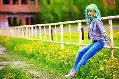 Chica joven feliz del retrato en festival del color del holi sobre una cerca vieja Fotos de archivo