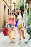Chica joven feliz dos que camina con los panieres Foto de archivo