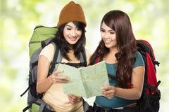 Chica joven feliz dos que va el vacaciones con la mochila y el mapa Imagenes de archivo