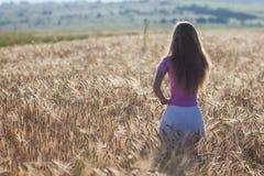 Chica joven feliz en campo de trigo de oro Goce de la mujer joven nacional Foto de archivo