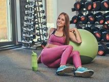 Chica joven feliz en la ropa de deportes rosada que se sienta en un piso con la bola de la aptitud y la botella de agua en el gim Fotografía de archivo