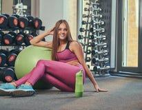 Chica joven feliz en la ropa de deportes rosada que se sienta en un piso con la bola de la aptitud y la botella de agua en el gim Foto de archivo