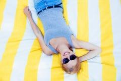 Chica joven feliz en las gafas de sol que mienten en la estera Fotografía de archivo libre de regalías