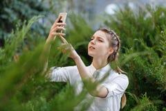 Chica joven feliz en parque con el teléfono en manos Imagen de archivo libre de regalías