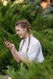 Chica joven feliz en parque con el teléfono en manos Foto de archivo libre de regalías