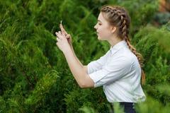 Chica joven feliz en parque con el teléfono en manos Imágenes de archivo libres de regalías