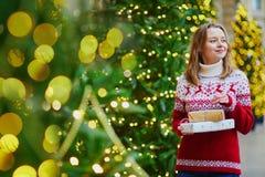 Chica joven feliz en suéter del día de fiesta con la pila de regalos de Navidad foto de archivo