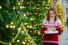 Chica joven feliz en suéter del día de fiesta con la pila de regalos de Navidad imagen de archivo