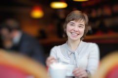 Chica joven feliz en un café Fotografía de archivo