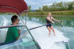 Chica joven feliz que aprende en el esquí acuático Imagenes de archivo