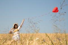 Chica joven feliz que camina en un campo de la guirnalda que lleva a cabo un corazón rojo b Imagen de archivo libre de regalías