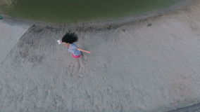 Chica joven feliz que circunda alrededor de sí misma en la playa cerca del río almacen de metraje de vídeo