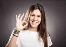 Chica joven feliz que da OK Foto de archivo libre de regalías
