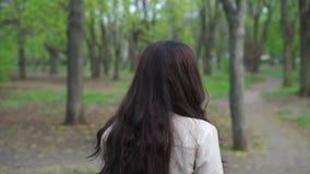 Chica joven feliz que da une vuelta y que da vuelta con una sonrisa en el parque almacen de metraje de vídeo